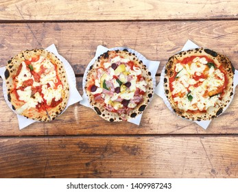 Aerial view of three different pizza types on rustic wooden table