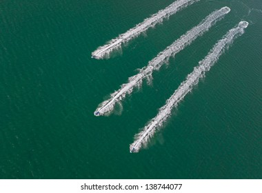 Aerial view of three jet boats and their wakes forming diagonal lines in the ocean.