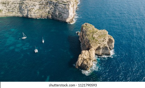 Aerial view of three white yacht sailing boats in the bay of deep blue mediterranean sea with rocky cliffs in Gozo, Malta. Shot from above. Travel concept