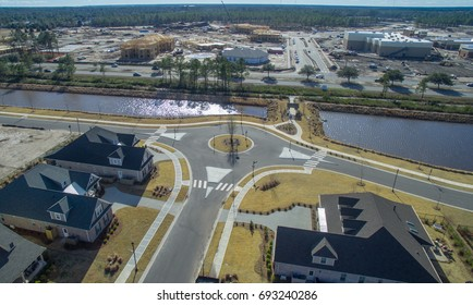 Aerial view of a three-way traffic circle in a new neighborhood.