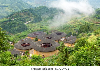 aerial view of Tianluokeng Tulou cluster with mist
