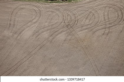 An aerial view of the tire tracks left by a tractor and planter working in a farm field.