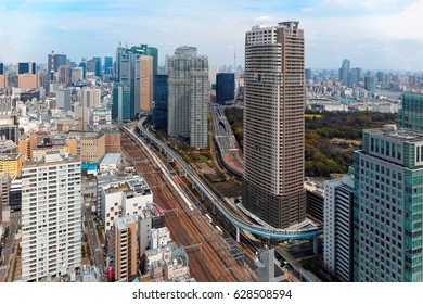 Aerial view of Tokyo Downtown with a beautiful city skyline under sunny sky, a high speed bullet train traveling on Shinkansen Railway & elevated Yurikamome Line running between high rise skyscrapers