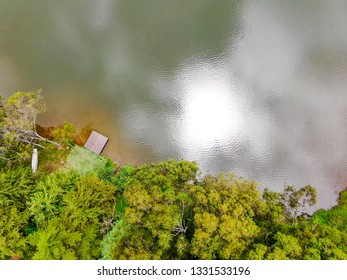 Aerial view top view of beautiful little wood  pier next the lake in tropical forest mountain. Monte Alegre Do Sul, Brazil. 02/05/2019