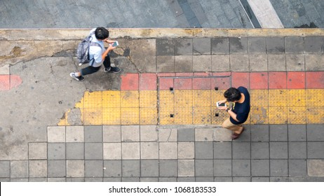 Aerial view and top view with blur man with smartphone is walking in business area with pedestrian street and red and yellow block walkway