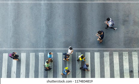 Aerial view and top view with blur man with smartphone walking converse with busy city crowd move to pedestrian crosswalk on business traffic road (Aerial photo, top view)
