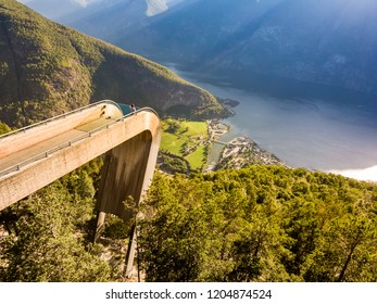 Aerial view. Tourist woman enjoying fjord view Aurlandsfjord landscape from Stegastein viewing point. Norway Scandinavia. National tourist route Aurlandsfjellet.