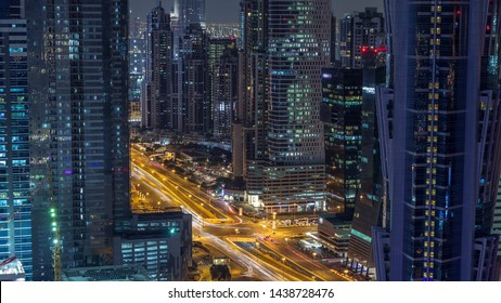 Aerial view of towers in Business Bay with traffic on the road night timelapse. Big modern city with skyscrapers and construction site. Downtown Dubai, United Arab Emirates.