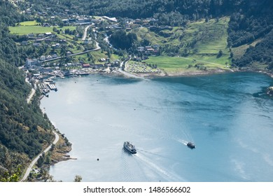 Aerial view of town of Geiranger fjord with arriving ships in Norway at a clear sunny day