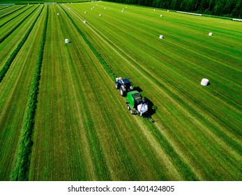 Aerial view of Tractor mowing green field in summer Finland.