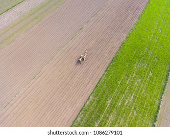 Aerial view of a tractor on a geometric agricultural field