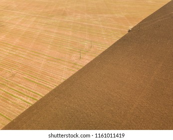 Aerial view of a tractor ploughing agricultural farmland, UK