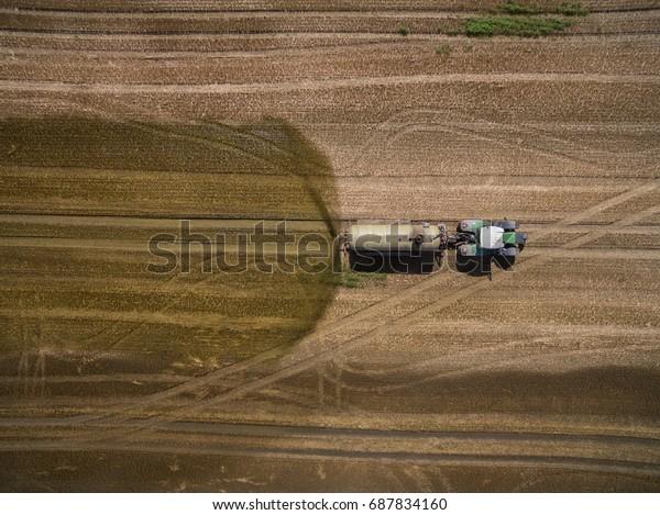Vista aérea de un tractor con un remolque fertiliza un campo agrícola recién arado con estiércol en Alemania