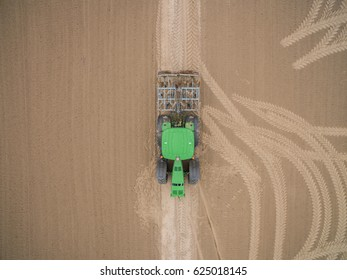 aerial view of a tractor at work cultivating a field in spring