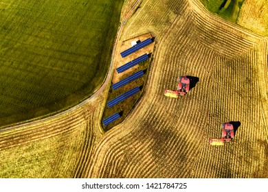 Aerial view of tractors working in cultivated field with solar panel