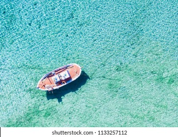 Aerial view of a traditional Greek fishing boat, a so called Kaiki, over turquoise sea in Greece
