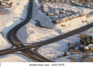 Aerial view of traffic intersection and houses in the snow.