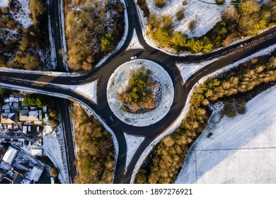 Aerial view of a traffic roundabout and road junctions on a snowy day in winter