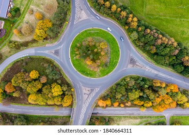 Aerial view of a traffic roundabout surrounded by trees in their autumn colours in the UK