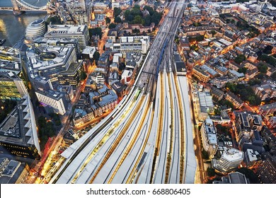Aerial view of train tracks entering London Bridge illuminated at dusk