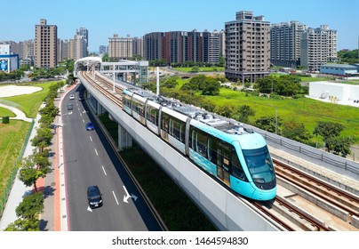 Aerial view of a train traveling on the elevated track of Danhai Light Rail System near Tamsui District Office Station with residential towers standing under sunny sky in background in New Taipei City