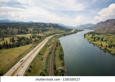 Aerial view of Trans-Canada Highway near Thompson River during a vibrant sunny summer day. Taken near Kamloops, BC, Canada.