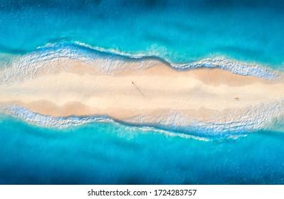 Luftsicht auf das blaue Meer mit Wellen auf beiden Seiten und Menschen auf dem Sandstrand bei Sonnenuntergang. Sommerreisen in Sansibar, Afrika. Tropische Landschaft mit Lagune, weißem Sand und Ozean. Top-Ansicht