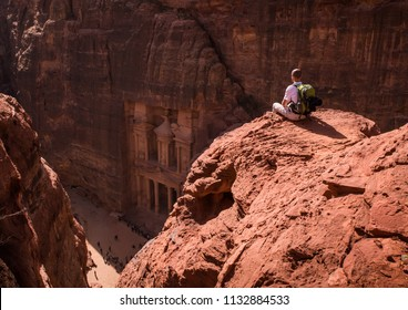 Aerial view of the Treasury with a hiker, solo traveler, young man backpacker sitting on a cliff after reaching the top, Al Khazneh in the ancient city of Petra, Jordan, UNESCO World Heritage Site