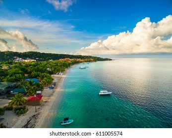 An aerial view of a tropical beach in Roatán Honduras early in the morning.