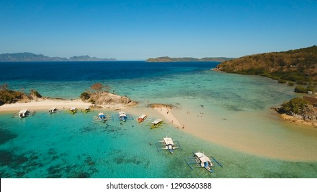 Aerial view of tropical beach on the Bulog Dos Island, Philippines. Beautiful tropical island with sand beach, palm trees. Tropical landscape: beach with palm trees. Seascape: Ocean, sky, sea. Travel