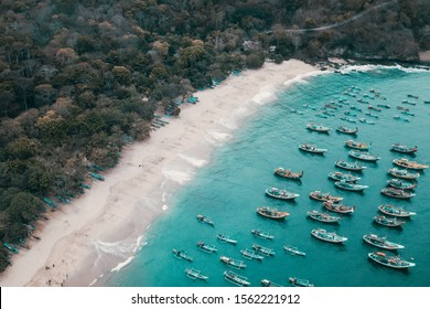 Aerial view of tropical forest and blue water beach with a traditional wooden fishing boats, taken at papuma beach, east java, indonesia
