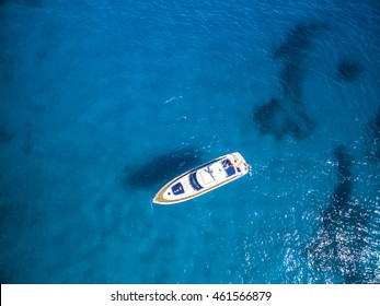 Aerial view of tropical island beach holiday yacht on blue reef ocean