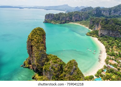 Aerial view of tropical island, white beach, turquoise lagoon, rocks and islands on horizon, Krabi, Railay, Thailand. Life in paradise. Travelling and holiday concept. People resting on the beach.