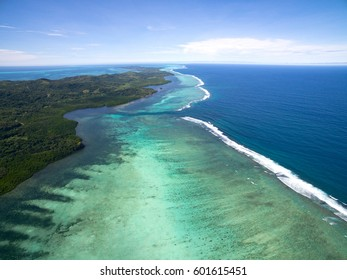 Aerial view of tropical reef and coastline disappearing at horizon
