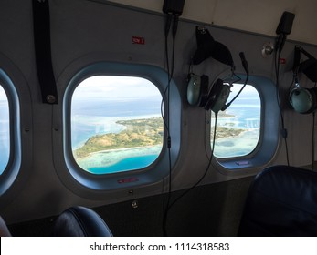 Aerial View of Tropical South Pacific Island Surrounded by Colourful Deep Blue Ocean Sea Reef from Inside Seaplane