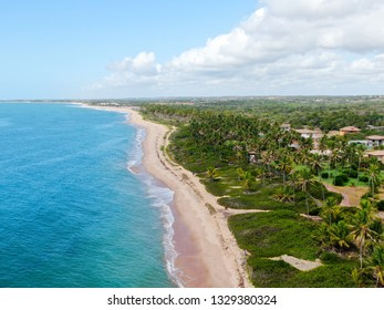 Aerial view of tropical white sand beach and turquoise clear sea water with small waves and palm trees background. Praia do Forte, Bahia, Brazil. Travel tropical concept