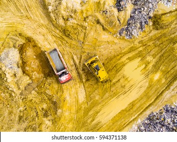 Aerial view of truck and bulldozer riding on muddy road trough a dump. Heavy industry from above. Industrial background from devastated landscape.