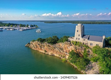 Aerial view of Tucker Tower on Lake Murray in Ardmore Oklahoma on a summer day with a houseboat in the distance