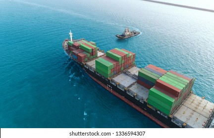 Aerial view Tug Boat come for drag Container ship to Crane bridge at seaport for unload Container to Container warehouse at blue sea. Logistics business, import export, shipping or transportation.