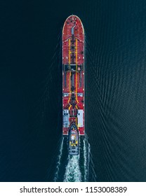 Aerial view of a tug boat pushing a barge carrying crude oil