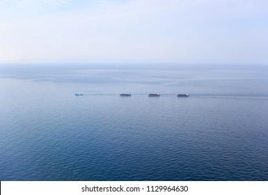 Aerial view of tugboat pulling three ships through vast blue ocean