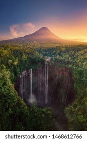 Aerial view of Tumpak Sewu waterfall and Semeru mountain at sunrise located in east java, Lumajang, Indonesia. Natural landscape background.