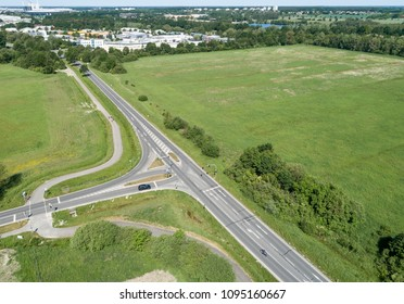 Aerial view of the turn-off of a ring road with the houses of the dominion in the background, near Wolfsburg