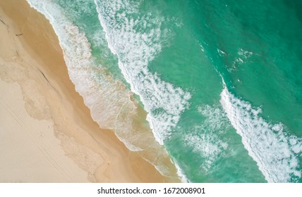 Aerial view of turquoise sea and beach, and yellow sand