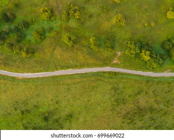Aerial view of twisting road among the forest and trees. Sunset field in Lithuania.