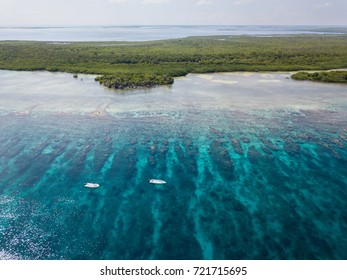An aerial view of two dive boats floating above the barrier reef along Turneffe Atoll in Belize. The area supports a wide variety of marine life and is popular among divers, snorkelers, and fishermen.