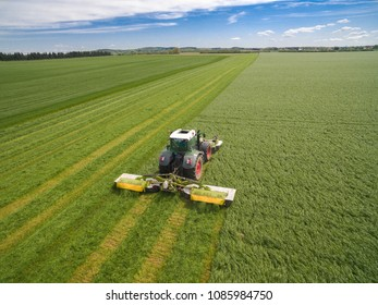 Aerial view of two modern tractors mowing a green fresh grass field on a sunny day with blue sky.