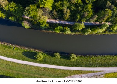 Aerial view of two roads on each side of the Isar river in a sprin morning. Bird view of Isar river banks near munich and the Alps with trees and forest around.