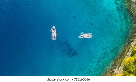 Aerial view of two sailing boats anchoring next to reef. Bird eye view, water sport theme.