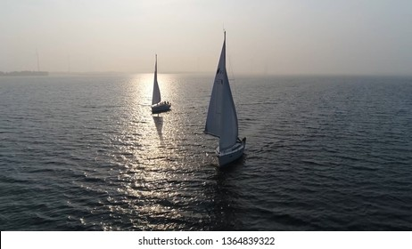 Aerial view of two sloops at sundown are sailing boats with single mast and fore-and-aft rig plus one head-sail the most common setup of modern sailboats is the Bermuda-rigged configuration